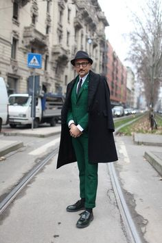 Try pairing a black overcoat with dark green tartan trousers for a classic and refined silhouette. Black leather tassel loafers will give your look an on-trend feel.  Shop this look for $297:  http://lookastic.com/men/looks/hat-pocket-square-tie-blazer-dress-shirt-overcoat-dress-pants-socks-tassel-loafers/4700  — Black Wool Hat  — Teal Pocket Square  — Black Tie  — Dark Green Plaid Blazer  — White Dress Shirt  — Black Overcoat  — Dark Green Plaid Dress Pants  — Black Socks  — Black Leather…