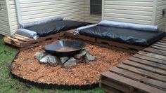 Fire pit and pallet sitting. I loved this. Only money i spent was for cushions covers and mulch. Palleys from any store u can get them. Cushions are your choice i found out futon mattress ( in trash) cut them down to size for cushions and used extra to make bolster pillows. Already had paint. Wheel borrow was old unused in shed and rocks came from side of road.