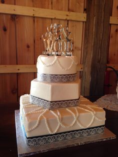 Three tier buttercream wedding cake with round, hexagon, and square tiers and pearls and lace detail.