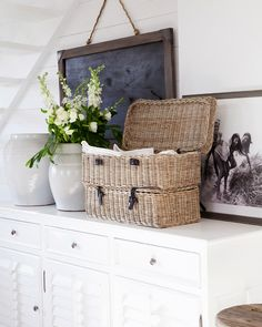 art, flowers, basket, old picture on a white chest of drawers