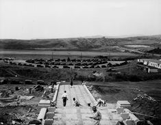 """(ca. 1928) - View of the new UCLA Westwood campus looking west from the top of Janss Steps. Workers are seen constructing the steps. The UCLA campus's """"Janss Steps"""" is named for two brothers, Harold and Edwin Janss of the Janss Investment Company who developed Westwood and also made it possible for UCLA to be built. The steps were donated to UCLA by the Janss brothers."""