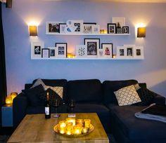Witte wandplankjes Ikea aan de muur in de woonkamer met fotolijstjes zwart wit met foto's en spreuken
