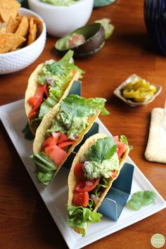 These spicy black bean tacos are the perfect easy dinner. The warmed corn shells are stuffed with chopped romaine, tomatoes, salsa, red onions, and guacamole. Vegan & gluten-free. | cadryskitchen.com