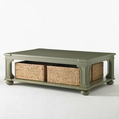 Low Country Coffee Table  This oversized coffee table in an aged green painted finish has routed detailing on the legs and four water hyacinth baskets to hold TV remotes and dog toys. #coffee table