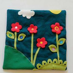 """Kytky na louce - didaktická hračka Toto je větší hrací deska o rozměrech 32x32 cm, je ušitá z bavlněné látky, má všitou vložku z dutého vlákna, aby byla měkká. Aplikace jsou z fleecu. Zelená ,,travička"""" není zcela přišitá, takže s ní lze pohybovat. Pokud je dítě ještě malé, nemusí se z podložky nic sundávat a dítě si pouze rozšiřuje slovní zásobu - kytička ..."""