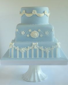 "Wedgwood Inspired Wedding Cake with handmade sugar stripes, bows, flowers, cameos and swags and piped royal icing detail. 6"" Vanilla sponge with raspberry preserve and vanilla buttercream. 8"" Chocolate fudge cake with Belgian chocolate buttercream. 10"" Rich fruit cake. As shown £390, serves 155 finger portions/ 95 dessert portions."
