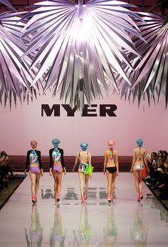 Models walked the runway beneath clusters of giant metallic palm leaves that swayed in the imaginary summer breeze.