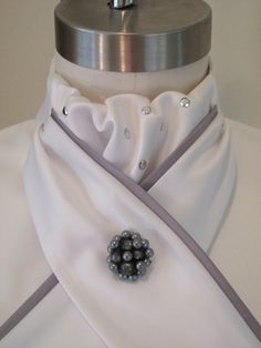 Show Hack and Dressage Embellished Ascot Dickie with silver nailheads and silver grey piped ties Ascot flips over collar and can also be kept behind the collar to make only the stock ties visible. Alll dickies have waist ties. Magnetic pin not included, for display purposes only.. Custom request us for different color piping. Fabric: 100% Polyester matte sateen w/ polyester sateen piping Back neck has 2 velcro Size: XS/13 adjustable neck S/15 adjustable neck M/16 adjusta...