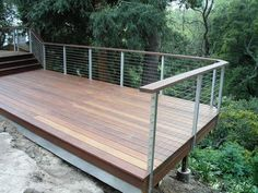 Cable railing shown with stainless side mounted posts and wooden top rail.