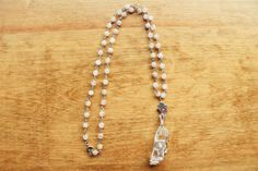 This necklace features a large raw quartz point wrapped with a unique design and strung on a handmade bead chain of rose quartz beads. There is also a