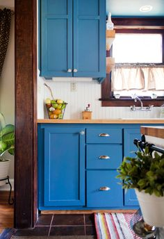 Another instance of darkly stained wood with blue cupboards and white walls