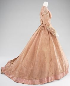 Evening Dress - Mme. Olympe, 1865 : Olympe Boisse was a French-born New Orleans dressmaker who regularly traveled to Paris to keep abreast of trend-setting French fashions of the time, such as those by Charles Frederick Worth and Emile Pingat. Mme. Olympe, as she was professionally known, initially was an importer of French goods but in time designed and sold her own garments. Her claim to fame is that, considering the date of this dress, she was one of the first, if not the first, American…