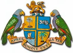 Dominica - Coat of Arms ~ The coat of arms of Dominica was adopted on July 21, 1961. It consists of a shield with two guardian sisserou parrots bracing the shield atop of which is a raging lion. The quadrants of the shield depict a canoe, a banana tree, a palm and a frog of the native species known as the mountain chicken. Below the shield is the national motto: Apres Bondie C'est La Ter (After God the Earth).