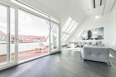 Una grande mansarda con zona giorno open space, arredamento minimalista e vista sulla città.