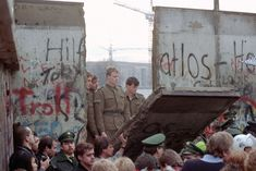 East German border guards look through a hole in the Berlin wall after demonstrators pulled down one segment of the wall at Brandenburg gate on November 11th, 1989. (AP Photo/Lionel Cironneau) #