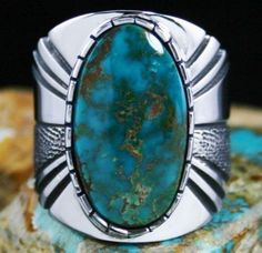 Leonard Nez Rare Gem Grade Blue Gem Turquoise Ring #LeonardNez A rare and gorgeous gem grade natural Blue Gem turquoise was chosen for this fine men's ring created by Leonard Nez. The cabochon glows with a marvelous depth of deep aqua blue-green with vibrant flecks of gold host rock matrix. This hue from the mine is the rarest and thought by many to be the most beautiful. It sits in a hand chiseled bezel atop a heavy ten gauge shank.