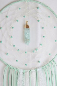 9 x 24 Dream Catcher wrapped in a mint faux suede, white hemp, howlite beads, a glass pendant in a mint color, white lace, and white pheasant