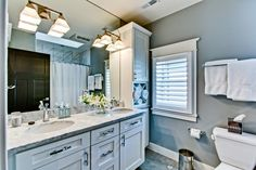 Craftsman-style cabinets are paired with gray countertops in this sophisticated, transitional bathroom. A large mirror helps visually enlarge the space, while a pair of gold sconces add contemporary style to the room.