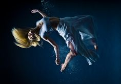 """Free Fallin - Joao Carlos """"When you actually shoot with strobes underwater, it looks fake. I tried to do the opposite: make it look real by faking it.""""     (The model is actually in a studio, jumping & throwing powder for the bubble effect.) - Awesome!"""