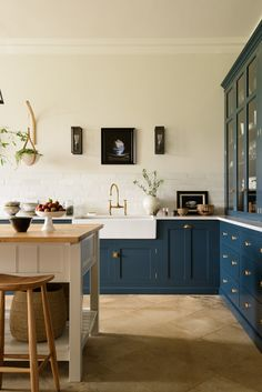 The kitchen island, painted off-white, is topped with oak. The Bum Stools are from deVOL.