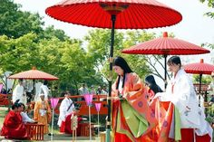 Men and women dressed in heian robes.