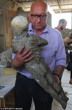 Restorers are working on the carefully preserved plaster casts of 86 of the Romans trapped in Pompeii in 79 AD, including children seemingly frozen in terror. Here, Stefano Vanacore, director of the laboratory at Pompeii Archaeological Site can be seen carrying the remains of a petrified child in his arms