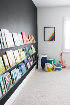 Library wall and color bins for toy storage. Love how this room incorporates all the colors of the rainbow. Make decorating with kids toys a whole lot easier!