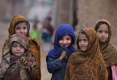 An Afghan refugee girl stands with others in an alley of a slum on the outskirts of Islamabad. (Muhammed Muheisen/Associated Press)