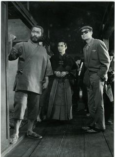 """Mifune (R), Yuzo Kayama, and Kurosawa, on set for """"Red Beard"""" (1965). /   Kurosawa was so insistent upon realism for the film that an entire town was built, and all the cabinets and drawers in the hospital were filled with medicine."""