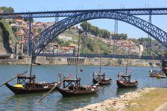 Vue du pont de Porto avec les pirogues sur le fleuve du Douro de jour.