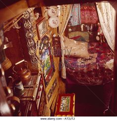 Horse brasses above kettle on stove in traditional narrow boat cabin with curtains and colorful fabric on bed - Stock Image