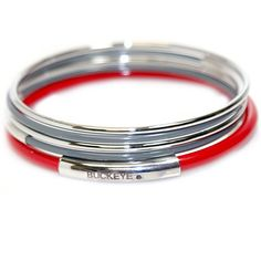 """Rosemarie Collections Women's Ohio State University Buckeyes 5 Layered Bangle Bracelet Set. Stylish set of 5 bangle bracelets in Ohio State University classic colors. 2 thin silver color bangles and 2 thin gray with silver band accent bangles. A thicker scarlet bangle features a silver band with """"Buckeye"""" engraving. Bracelet openings measure approx 2.75 inches across. Officially Licensed Collegiate Product."""