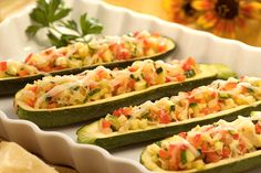 5 medium zucchini, halved lengthwise 3 tbsp Butter 1 medium onion, chopped 1 small red bell pepper 3 cloves garlic, finely chopped 1/2 tsp dried oregano leaves 1/4 cup grated Parmesan cheese  Directions Preheat oven to 375 Scoop out zucchini pulp, put zucchini on baking sheet, coarsely chop remaining zucchini and pulp, saute with onion 5min add peppers and spices 1min more, spoon mixture into halves, top with cheese, bake 30mins.