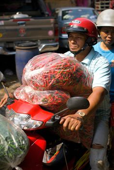 man driving off with bags full of chilies, Pak Klong Talat  market, Bangkok, Thailand