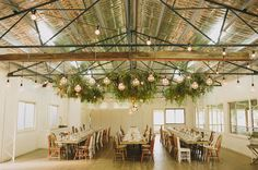 this indoor space has been transformed with the use of hanging evergreen and lighting. the order of the communal tables gives structure to the design but the mismatched chairs make it playful.