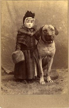 Vintage studio portrait of beautifully dressed little girl and her large dog.