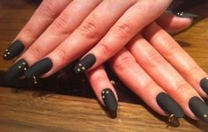 Matte black nails with studs and piercing