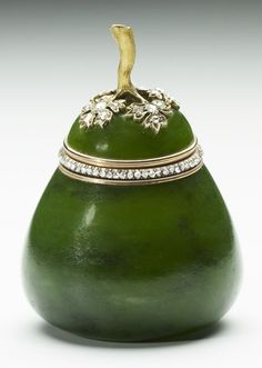 Carved from nephrite, this Fabergé pot replicates the form of a pear, complete with reeded gold stem terminating in a diamond and leaves in gold, highlighted with diamonds. The rim of the base is also set with a band of rose diamonds. Workmaster Michael Perchin, 1903. Probably acquired by King Edward VII or Queen Alexandra.