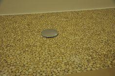 Dettaglio di un piatto doccia realizzato in resina epossidica trasparente con inserimento di ciotoli di Botticino. Detail of a shower tray made of Botticino pebbles in epoxy resin.