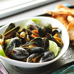 I love to set a big bowl of freshly-steamed mussels down in the middle of a dinner party and watch what happens. Some guests dive in with gleeful abandon while the shellfish newbies hang back to see how it's done. Either way, soon everyone is grabbing mussels from the bowl, slurping from the shells, and fighting over the last chunks of bread to sop up the sauce. It's a happy, playful, messy scene that never fails to get the party going.