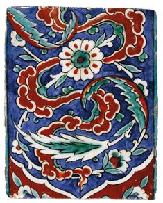 A POLYCHROME IZNIK TILE, TURKEY, 16TH CENTURY decorated in relief iron red and viridian green outlined in black with a design of stylised cloud bands and between scrolling saz leaves and rosettes on an underglaze cobalt blue ground 19.5 by 15.5cm.