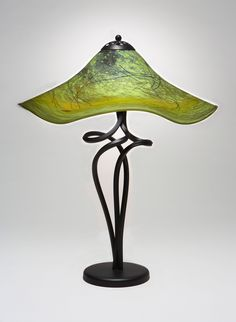 Mossy Green Spiral Lamp by Joel and Candace Bless. An elegant and colorful table lamp has a unique ''Mossy'' pattern glass shade. To create the look of moss in glass the artists use traditional glassblowing methods to overlap and incorporate glass colors to achieve various tones of greens with subtle touches of red and brown. These colors soften when lit internally. For the base they employ a unique metal-bending technique, then a final form is assembled in which the elegance and simplicity…