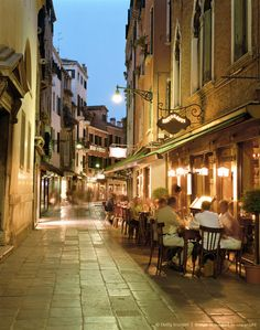 Italy, Venice, restaurants along cobbled street, dusk