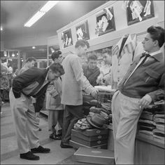 Young Men's Fashion in the '50's ~ young men looking through clothes. Casual pants and shirts, and jackets were pretty much a part of their lives!
