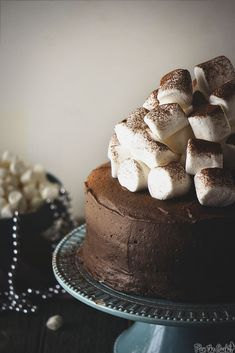 This is a double-decker classic chocolate cake with a fun marshmallow creme center and smooth chocolate frosting, polished off with a mountain of marshmallows and a dusting of cocoa powder.