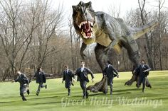 """Wait, WHAT? Okay, so this was someone's staged groomsmen photo for a wedding...all I can say is, """"Why?"""" Hilarious, though.......it'd be more awesome if it were a velociraptor or a pterodactyl....and if the bride were around, """"shooting"""" it with a machine gun xDDDD"""