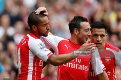 Theo Walcott of Arsenal scores his team's first goal with his team mates Santi Cazorla and Alexis Sanchez during the Barclays Premier League match between Arsenal and West Bromwich Albion at Emirates Stadium on May 24, 2015 in London, England.