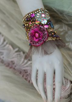 Romantic ornate wrist wrap inspired by splendor of baroque era; slightly asymmetric due of salvaged 1920 silk brocade piece used as base.Cuff is adorned with hand embroidered and beaded lace applique in shades of magenta and wine; embroidery with vintage colorful silk threads, vintage ab