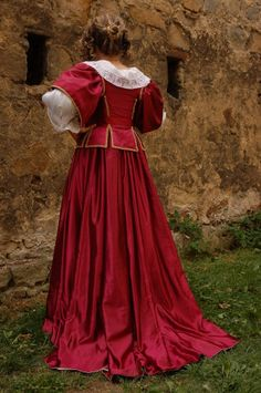 Baroque Overgown        For a formal or court dress, an overgown is worn over the underbodice and the petticoat. This overgown is made of red satin with white damask lining and consists of the skirt pleated by cartridge pleating and the open bodice laced by red ribbon with short sleeves. In the waistline, which is typically quite high, is a ribbon sash, on which some necessary things can be fastened, for example a fan. The whole dress is decorated with laces, ribbons, braids and pearls (of cours