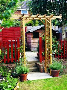 An+outside+wood+arbor+with+trellis+panels+provides+a+sturdy+frame+for+a+traditional+rose+arch+outside+the+backyard+garden.